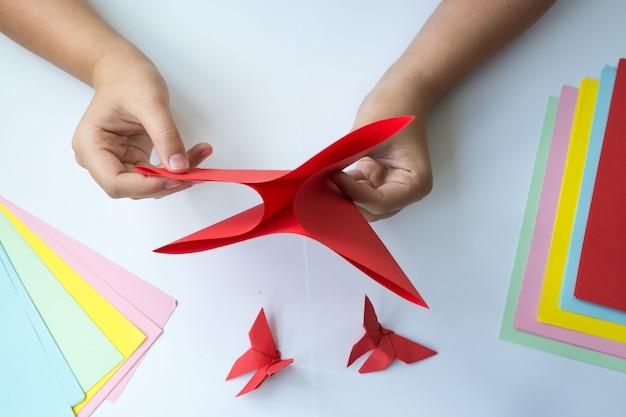 Kinderhände machen origami einen schmetterling.