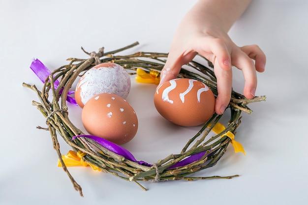 Kinderhände malen eier mit weißer farbe.