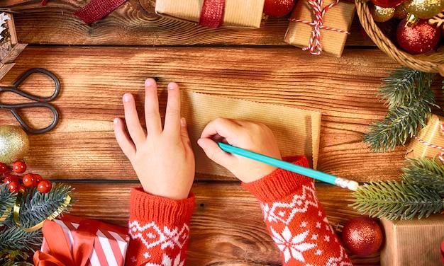 Kinderhände mit brief an den weihnachtsmann