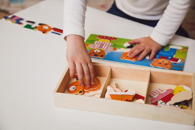Kinderhände mit buntem brettspiel auf dem weißen tisch. kind spielt am tisch. frühe entwicklung eines kinderkonzepts.