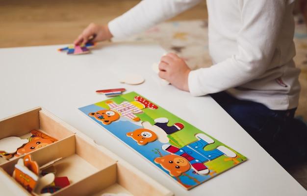 Kinderhände mit buntem brettspiel auf dem weißen tisch.