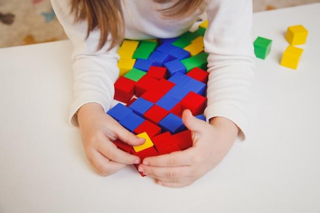 Kinderhände mit bunten würfeln auf dem weißen tisch. kind spielt am tisch. frühe entwicklung eines kinderkonzepts.