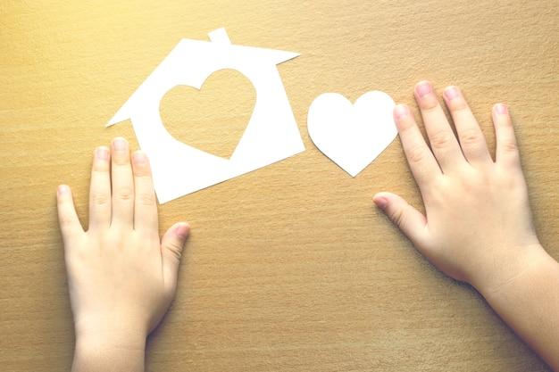 Kinderhände mit kleinem modell des hauses und des herzens auf hölzernem hintergrund