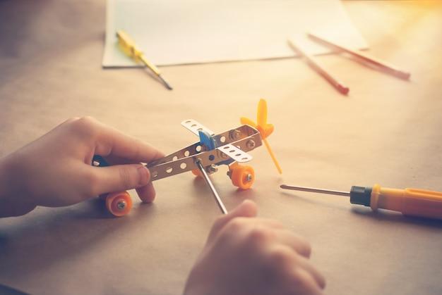 Kinderhände mit spielzeugeisenflugzeug. metallbauer mit schraubendreher. träume, spiele und erschaffe