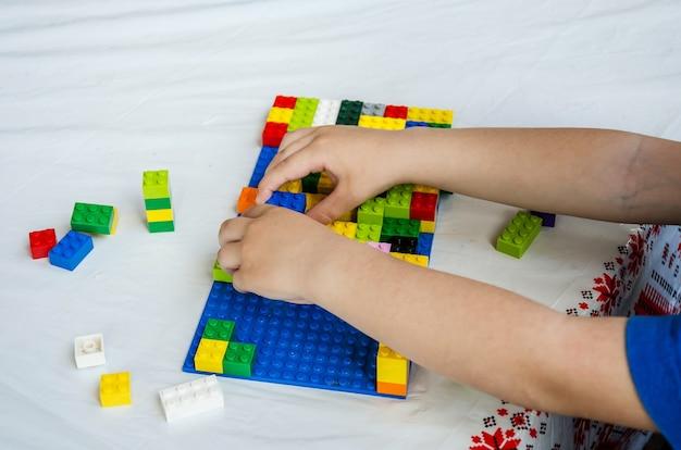 Kinderhände spielen den konstrukteur.