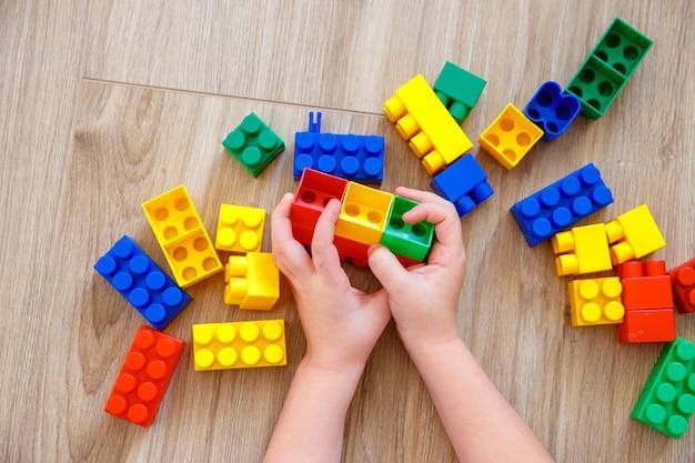 Kinderhände spielen mit bunten spielzeugblöcken. kinderspieldesigner.