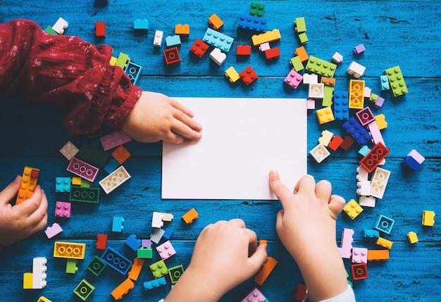 Kinderhände spielen mit farbigen spielsteinen