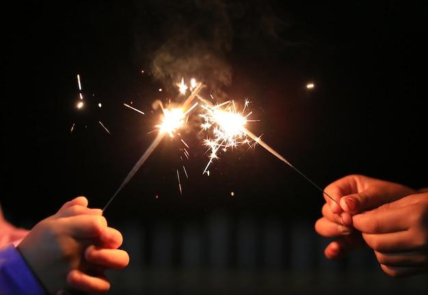 Kinderhände spielen mit feuer wunderkerzen auf dem festival.