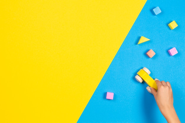 Kinderhände spielen mit hölzernem spielzeugauto auf blauem und gelbem hintergrund, draufsicht