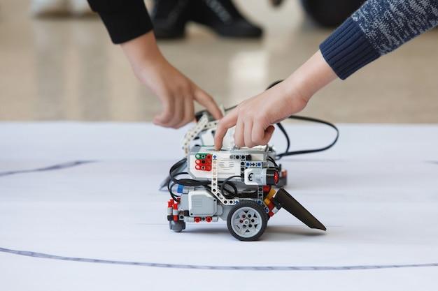 Kinderhände steuern roboter aus blöcken
