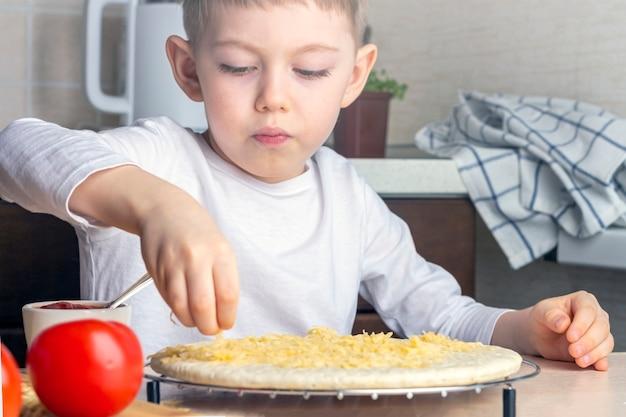 Kinderhände streuen käse auf pizzateig. prozess des kochens hausgemachter pizza durch kind. vorschulkinderfähigkeiten, kleiner helfer. familienfreizeit.