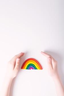Kinderhände um plastilin-regenbogen-lgbt-familienkonzept draufsicht farben der hellen hintergrundkopie der homosexuellen flagge oben