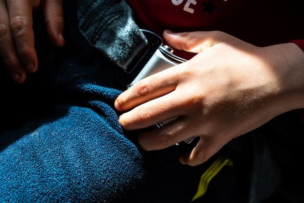 Kinderhand auf dem sicherheitsriegel eines flugzeuggurts.