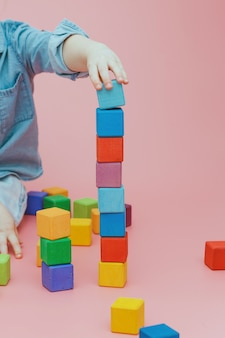 Kinderhand baut einen turm aus hölzernen farbigen würfeln.