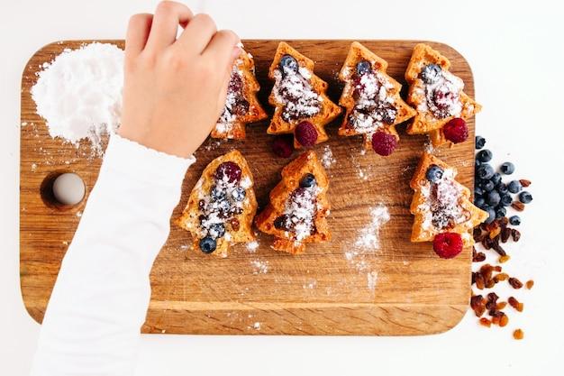 Kinderhand bestreuen kekse mit zuckerpulver