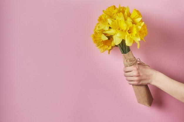 Kinderhand, die blumen auf einem rosa hintergrund hält. blumenstrauß zum geburtstag, mutter oder valentinstag.