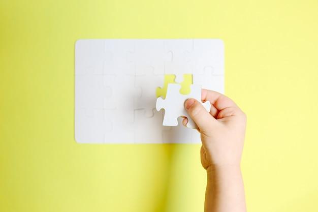 Kinderhand, die das letzte stück des weißen puzzles auf gelbem tisch hält