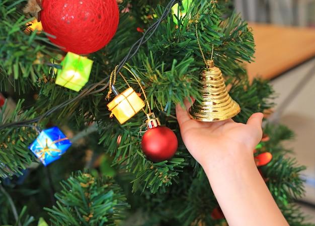 Kinderhand, die dekorative glocke auf weihnachtsbaum hält. frohe weihnachten und happy new year-konzept.