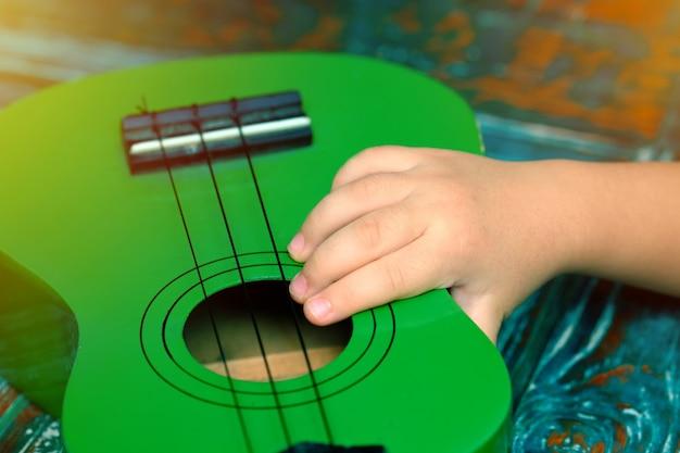 Kinderhand, die eine kleine ukulele hält