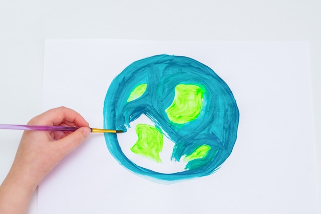 Kinderhand, die einen planeten erde mit einer weltkarte mit aquarellen auf weißem papier zeichnet. konzept für frieden und tag der erde. ansicht von oben.
