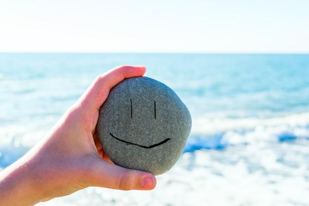 Kinderhand, die einen stein mit lächelndem gesicht neben dem meer an einem sonnigen tag hält