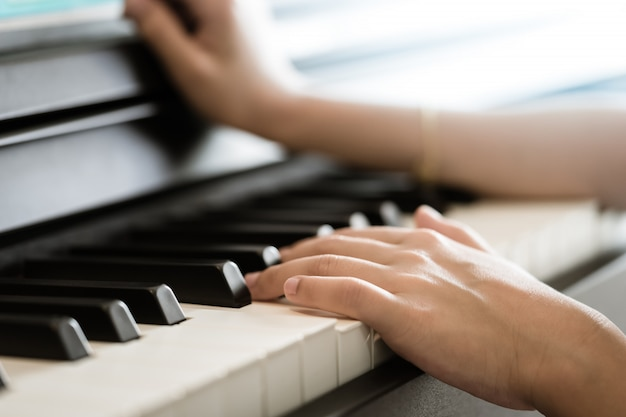 Kinderhand, die elektrisches klavier der musiktastatur spielt