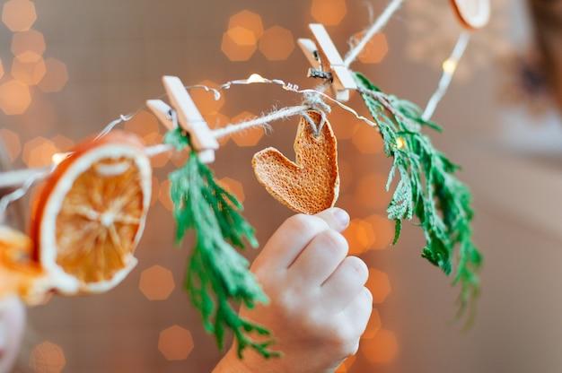 Kinderhand, die getrocknetes zitrusscheibenherz auf weihnachtsgirlande hält