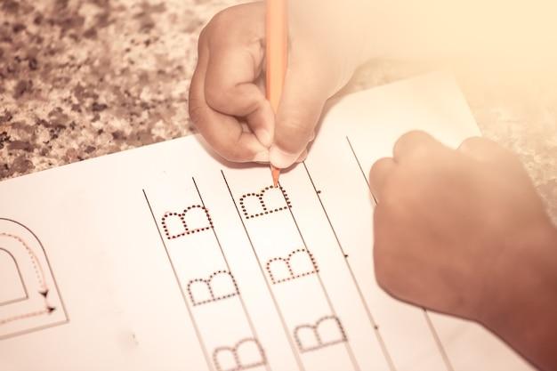 Kinderhand, die ihre hausaufgaben mit zeichenstift schreibt