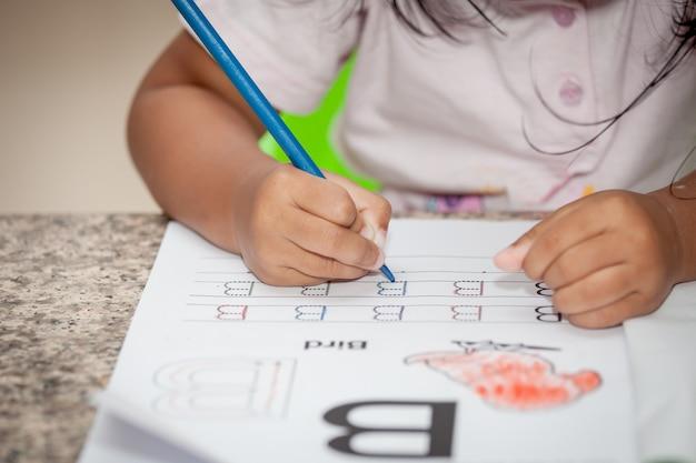 Kinderhand, die ihre hausaufgaben mit zeichenstift zeichnet