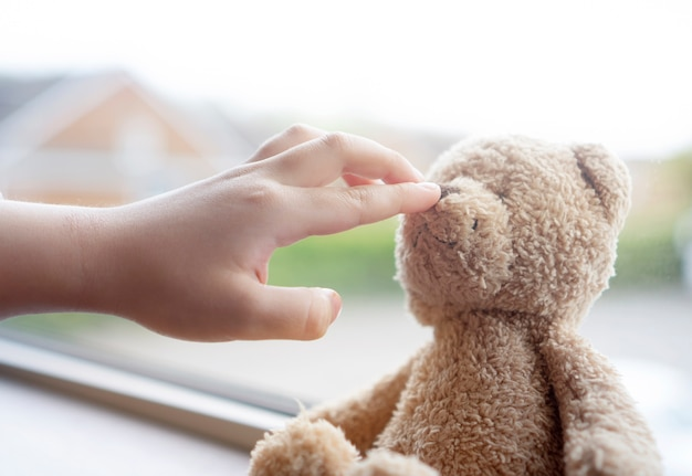 Kinderhand, die mit teddybärnase spielt