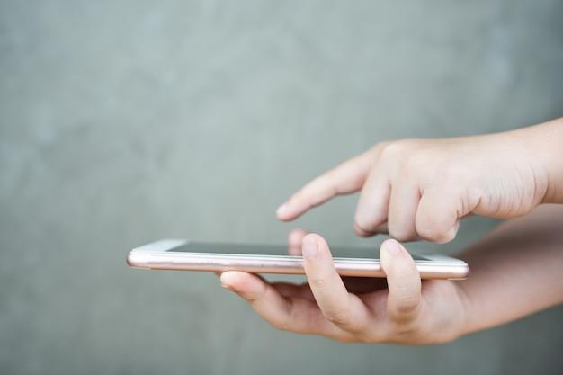 Kinderhand, die mobiles smartphone mit touchscreen auf grauem beton hält