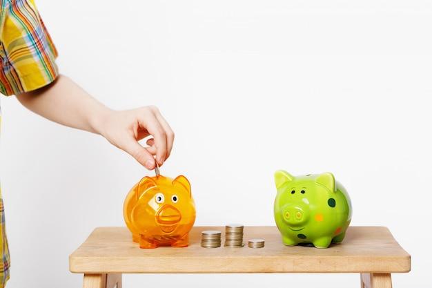 Kinderhand, die münze in ein sparschwein einsetzt.