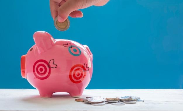 Kinderhand, die münze in sparschwein mit münzen dazu auf holztisch setzt