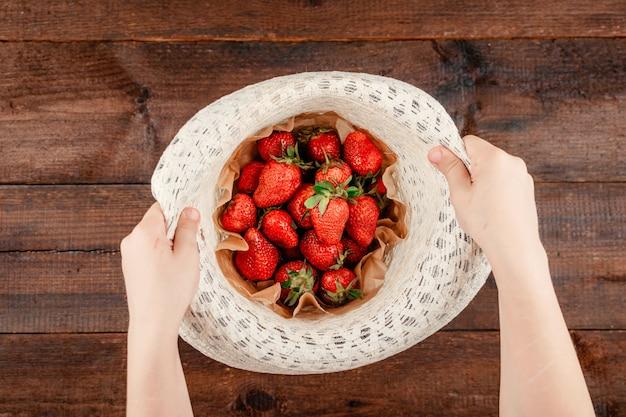 Kinderhand, die organische erdbeeren im runden hut hält