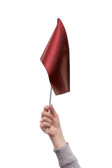 Kinderhand, die rote fahne lokalisiert auf weißem raum hält.