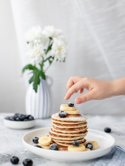 Kinderhand greift nach einem stapel pfannkuchen mit beeren. leckeres hausgemachtes frühstück. vertikales bild