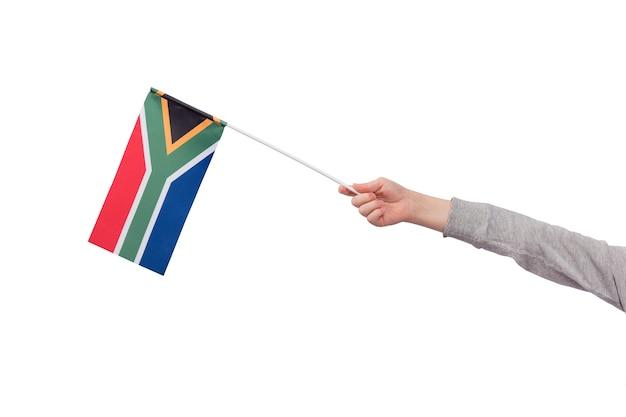 Kinderhand hält flagge von südafrika isoliert auf weißem hintergrund. attrappe, lehrmodell, simulation