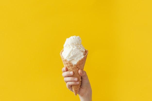Kinderhand hält köstliche vanille-eistüte auf einem hellen gelb mit kopierraum