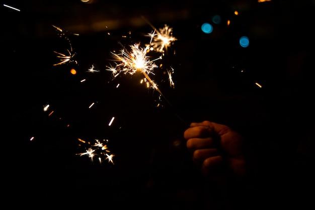 Kinderhand hält wunderkerze, die nachts brutzelt und glänzt.