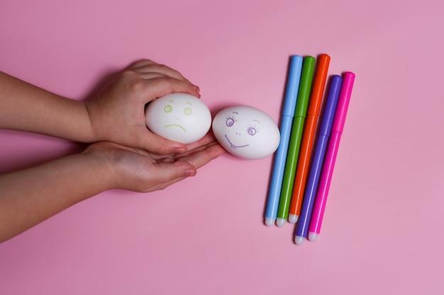 Kinderhand hält zwei eier traurig und fröhlich.