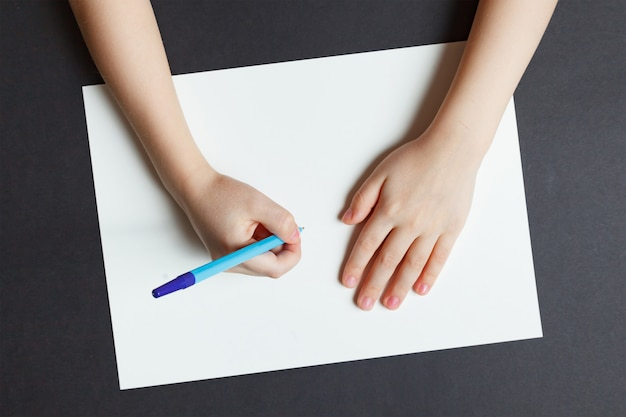 Kinderhand mit einem stift auf einem weißbuch
