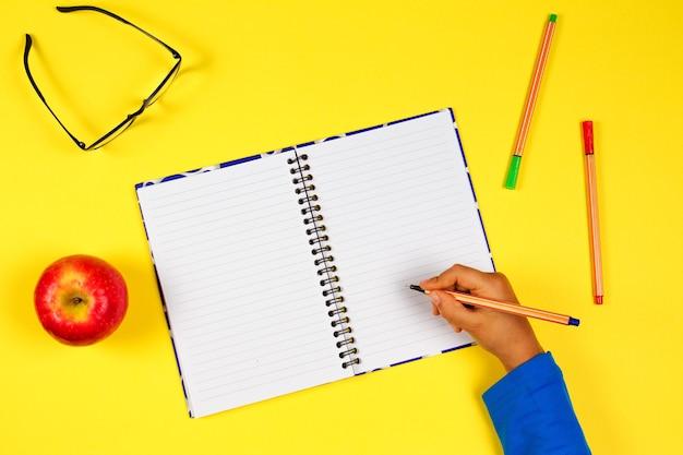 Kinderhand mit offenen notizbuchstiftgläsern und frischem apfel auf gelbem hintergrund