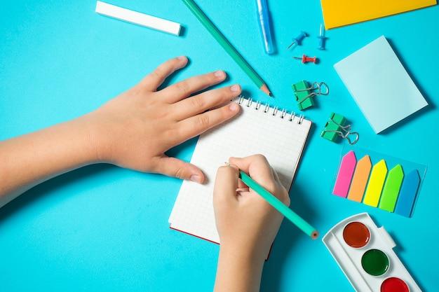 Kinderhand schreibt in ein notizbuch in komposition mit aquarell, bleistift, notizbuch, lineal, radiergummi. isometrisches konzept auf blauem hintergrund. pop-art. schulmaterial. overhead. zurück zum schulkonzept