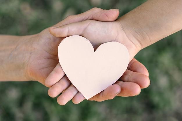 Kinderhand und alte großmutter halten herz. konzeptidee der liebesfamilie, die kinder und ältere leute großmutter freundschaft zusammengehörigkeit schützt