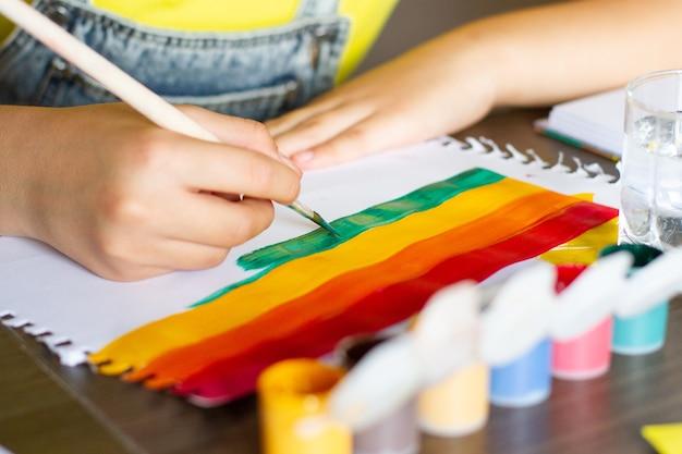 Kinderhandzeichnung, die bunten regenbogen malt