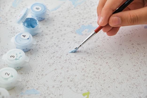 Kinderhandzeichnung mit pinsel auf nummerierter leinwand