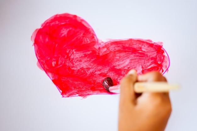 Kinderhandzeichnung und malte ein herz für die karte des valentinsgrußes mit spaß