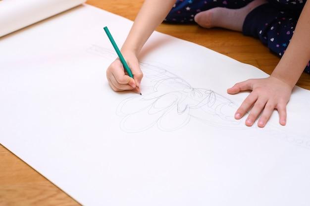 Kinderhobby. ein kleines mädchen malt mit einem bleistift auf papier, das zu hause auf dem boden sitzt.