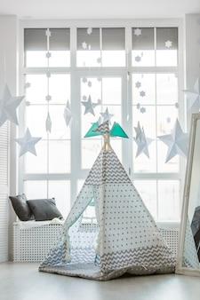 Kinderhütte im zimmer. innenraum des kinderzimmers. das schlafzimmer des babys. zelthütte für kinderspiele. feiertagsentwurf in boho-art, eine magische geburtstagsfeier, schöne indische hütte