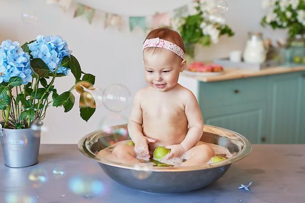 Kinderhygiene. shampoo, haarbehandlung und seife für kinder. kind, das in der großen wanne badet. baby girl wash, säuglingshygiene, gesundheit und hautpflege. baby im bad.